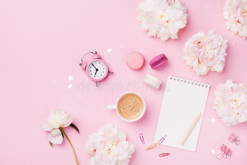 Kaffee, Makronen, Wecker, Bürozubehör, Pfingstrosenblumen und leeres Notizbuch Modefrauenarbeitsschreibtisch Flache Lage stockfotos