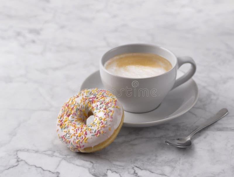 Kaffee mit buntem Donut im wei?en Marmorhintergrund lizenzfreies stockfoto