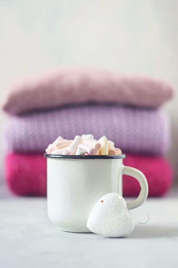 Kaffee mit Eibischen in der weißen emaillierten Metallschale und im weißen Herzen auf dem Hintergrund des Stapels rosa gestrickte lizenzfreie stockfotos
