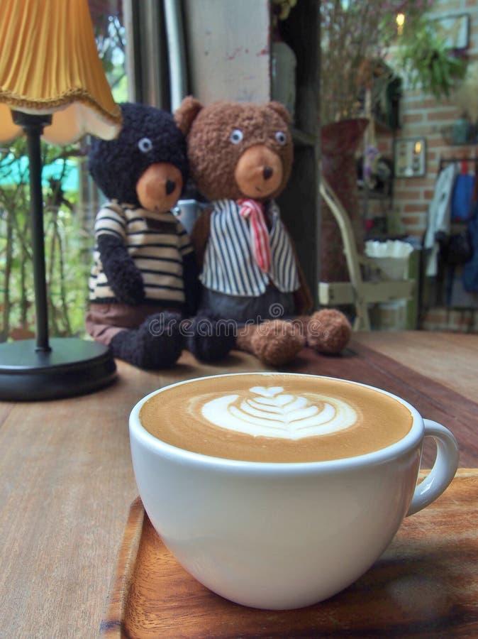 Kaffee mit Lattekunst und zwei tragen Puppen lizenzfreies stockfoto