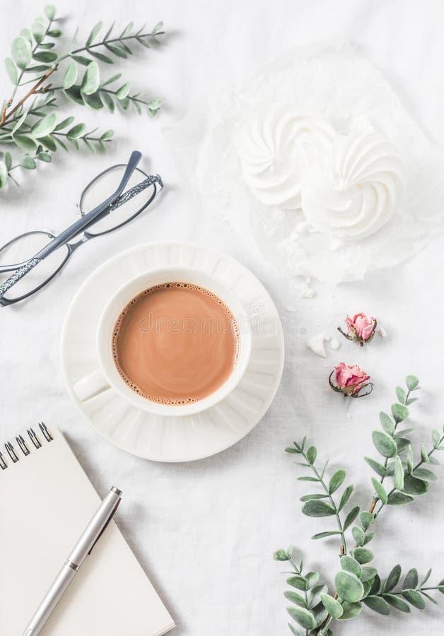 Kaffee mit Milch, Meringen, Blumen, leeres Notizbuch, Gläser auf weißem Hintergrund, Draufsicht Weibliches Tabelleninspirationsfr stockbilder