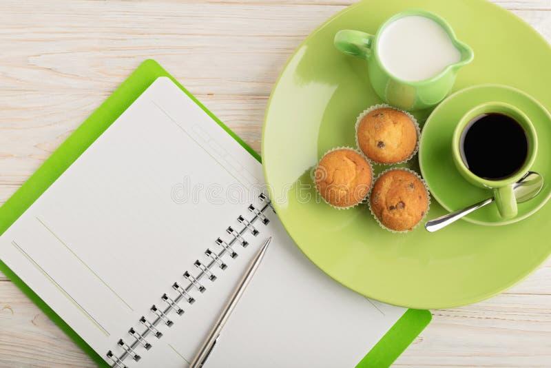 Kaffee mit Milch, Muffins und Notizblock auf hölzernem Hintergrund lizenzfreies stockbild