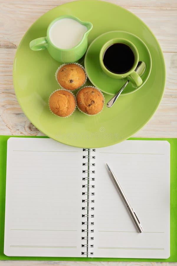 Kaffee mit Milch, Muffins und Notizblock auf hölzernem Hintergrund lizenzfreies stockfoto