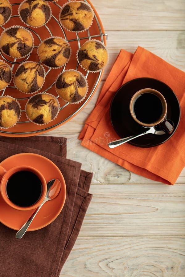 Kaffee mit Muffins auf einem hellen hölzernen Hintergrund lizenzfreies stockfoto