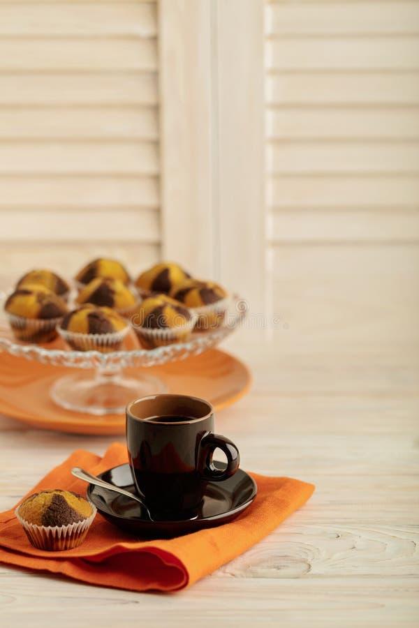 Kaffee mit Muffins auf einem hellen hölzernen Hintergrund lizenzfreie stockfotografie