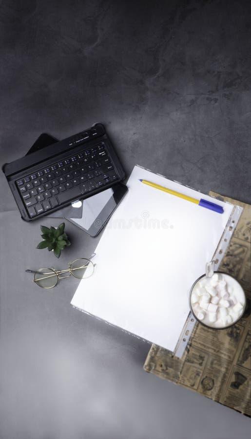 Kaffee mit Stift, weißes papper, Gläser, Hefter, Kaktus, Kaffee und Laptop, Kreditkarte auf konkreter Tabelle mit Zeitung lizenzfreie stockfotos