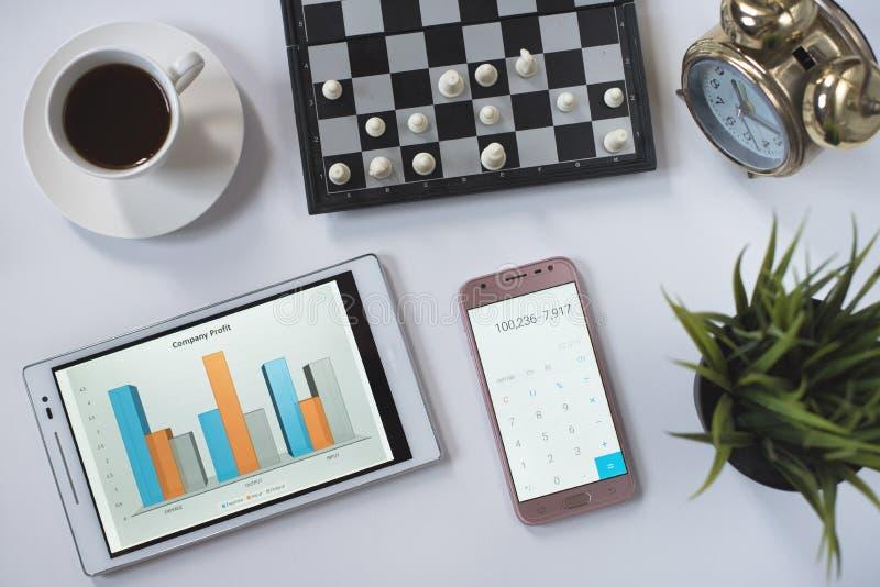 Kaffee, Schach, Telefon, Uhr und Digital-Tablet mit Geschäftsdiagramm auf weißer Ebenenlage lizenzfreie stockfotos