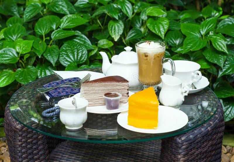 Kaffee, Tee, Schokoladenkreppkuchen und orange Kuchen lizenzfreie stockbilder
