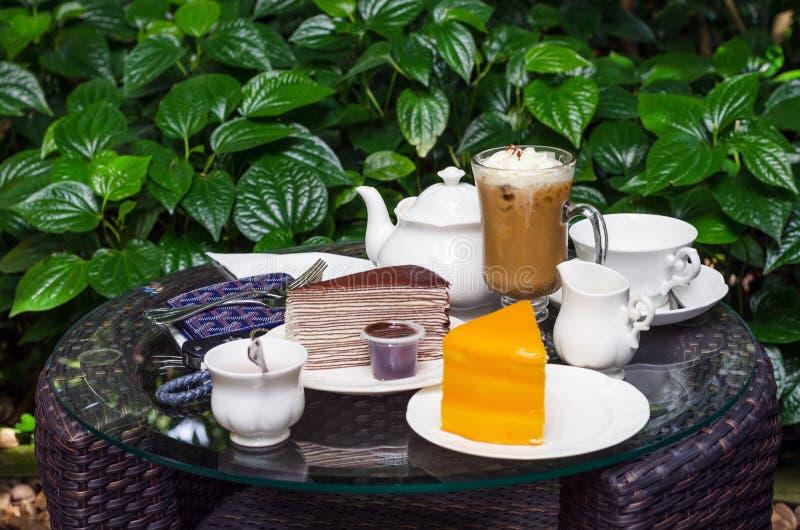 Kaffee, Tee, Schokoladenkreppkuchen und orange Kuchen auf Tabelle lizenzfreies stockfoto