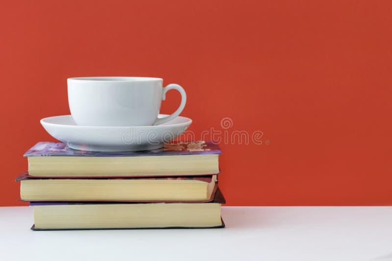 Kaffee und Bücher auf einem roten Hintergrund stockbilder