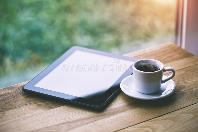 Kaffee und digitale Tablette auf Holztisch stockfoto