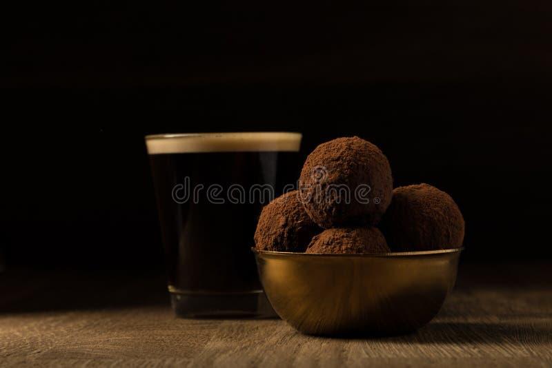 Kaffee und dunkle Schokoladentrüffeln in der goldenen Schüssel auf hölzernem Hintergrund lizenzfreie stockfotos