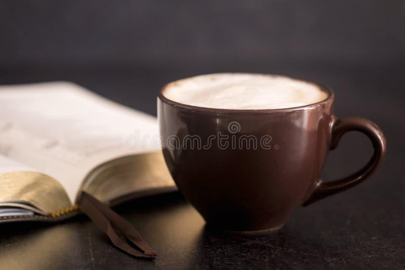 Kaffee und eine Bibel auf einer Schiefer-Tischplatte stockfoto