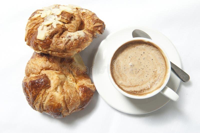 Kaffee und Hörnchen auf weiße Tabellen lizenzfreie stockfotos