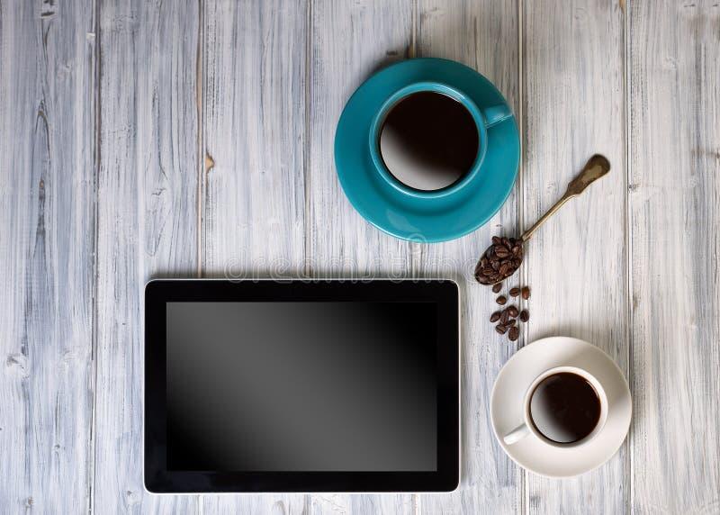 Kaffee und Tablette auf dem Tisch stockfotografie