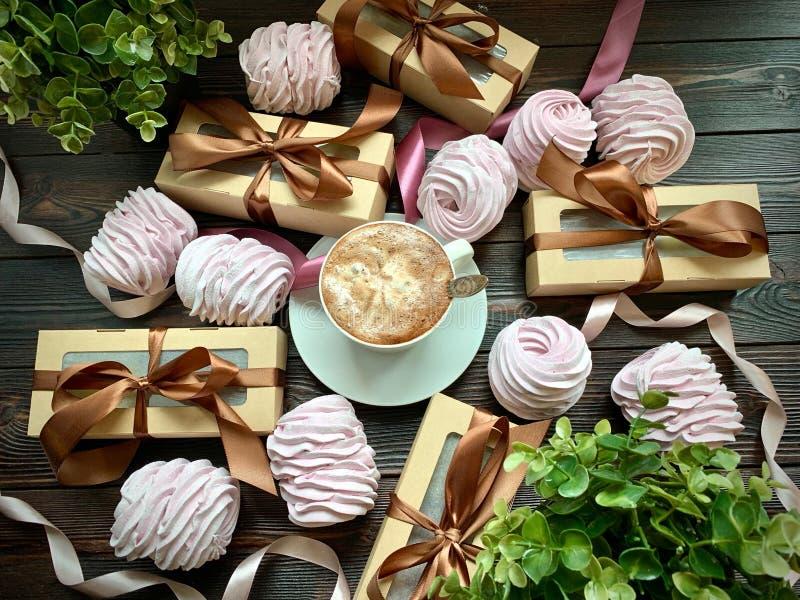 Kaffee wird auf einer Tabelle mit rosa Eibischen und Geschenken mit einem braunen Bogen ausgebreitet lizenzfreies stockbild