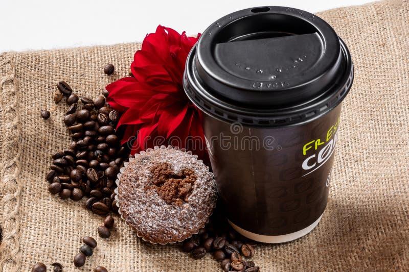 Kaffee zum Mitnehmen-Konzept Schale mit Kaffee, Muffin, roter Blume und Kaffeebohnen lizenzfreies stockbild