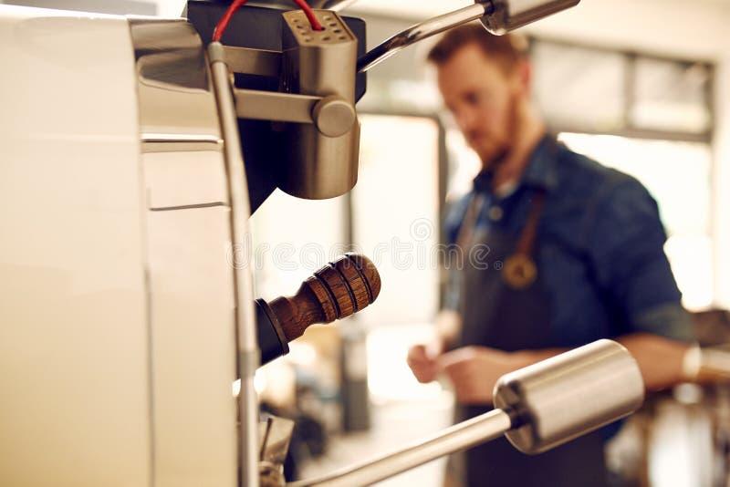 Kaffeebohne-Bratmaschine mit Mann im Hintergrund lizenzfreie stockfotos