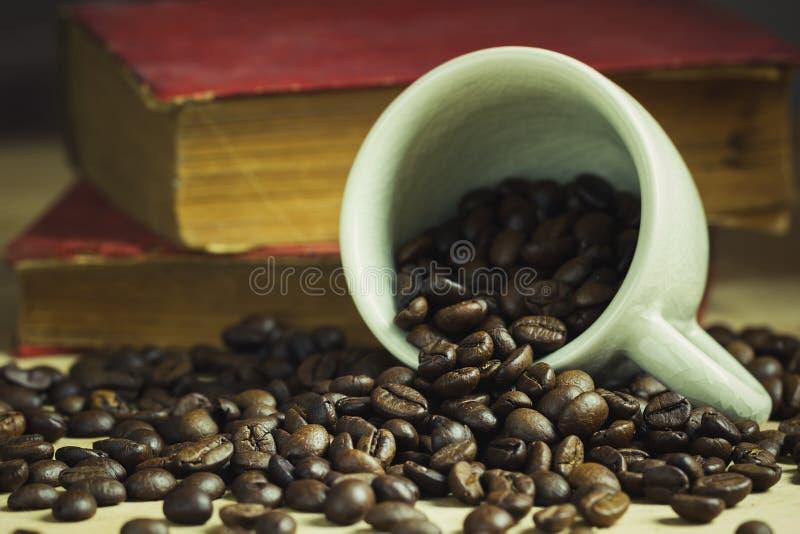 Kaffeebohne in gekippter keramischer Schale und in altem Buch legte hinten lizenzfreies stockbild