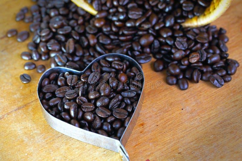 Kaffeebohne-Herzform auf Holztisch stockfotografie