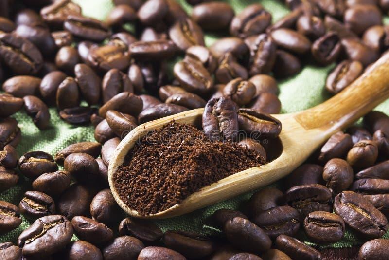 Kaffeebohne- und gemahlenerkaffee in einem hölzernen Löffel lizenzfreies stockbild