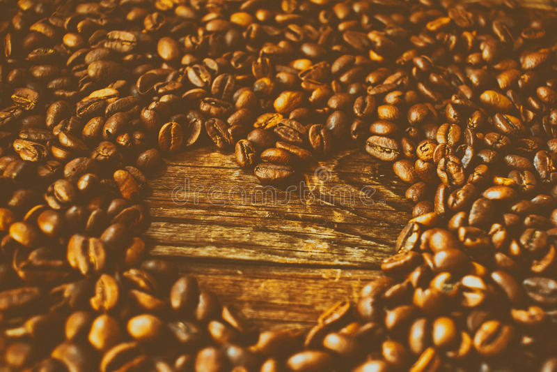 Kaffeebohnen angeordnet in einer Innerform Der Effekt des Filmkornes stockfotos