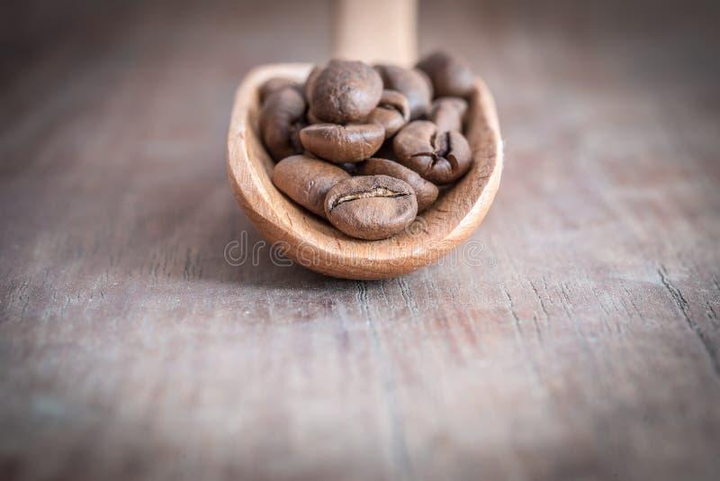Kaffeebohnen auf dem Löffel und hölzernem Hintergrund, flach tief vom fie stockfoto