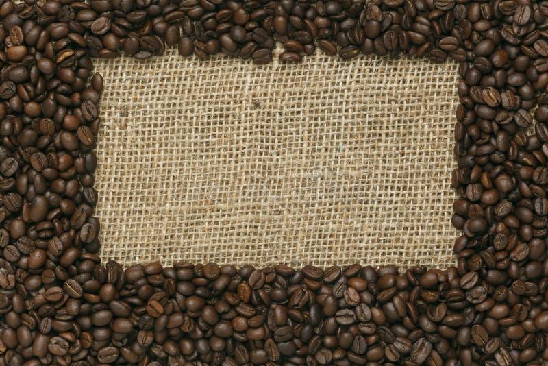 Kaffeebohnen auf Jutefaserhintergrund stockfotos