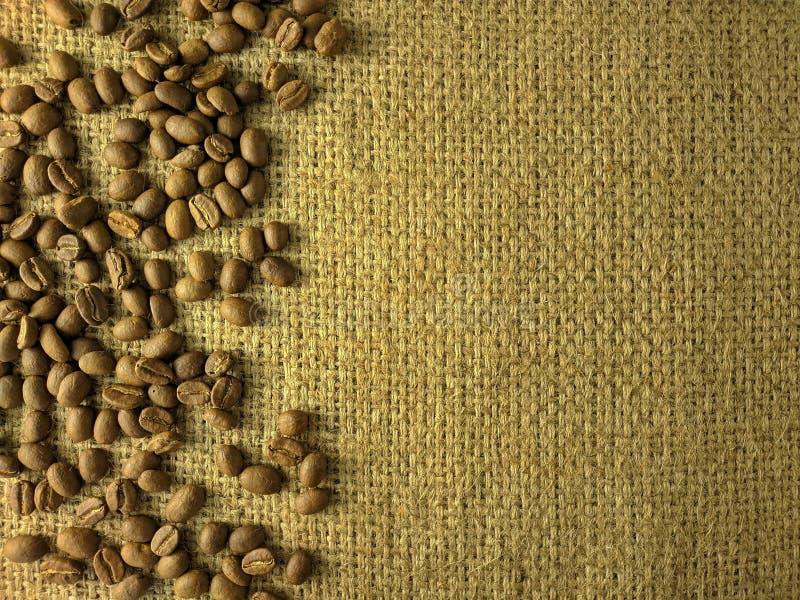Kaffeebohnen auf Juteleinwandbeschaffenheit stockbild