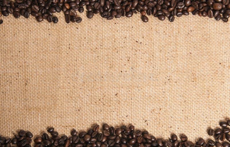 Kaffeebohnen auf Sack des groben Sackzeugs stockbild