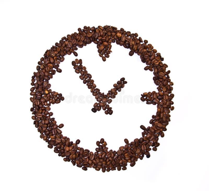 Kaffeebohnen conventionalized zur Borduhr stockfotografie