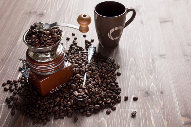 Kaffeebohnen in der Kaffeemühle und in der Schale auf braunem hölzernem Hintergrund lizenzfreie stockfotografie