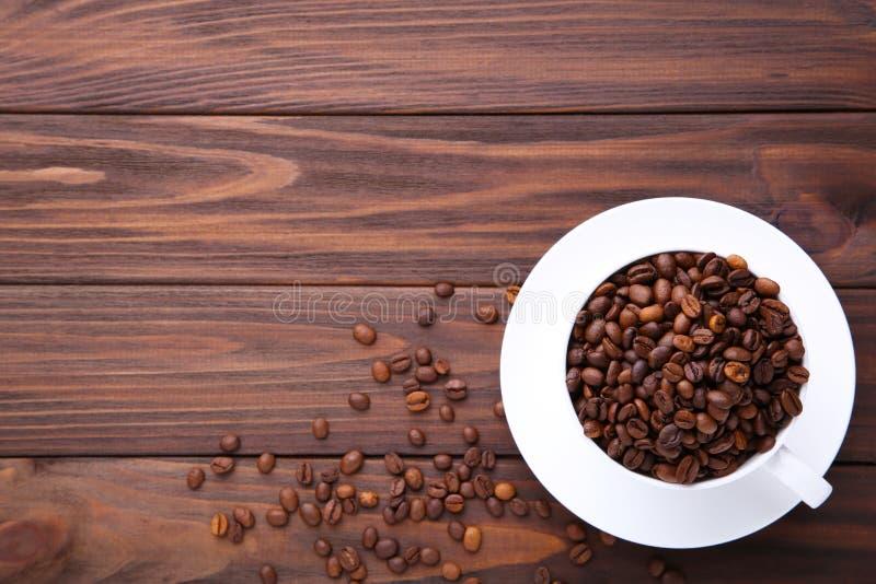 Kaffeebohnen in der Schale auf braunem hölzernem Hintergrund lizenzfreie stockfotografie