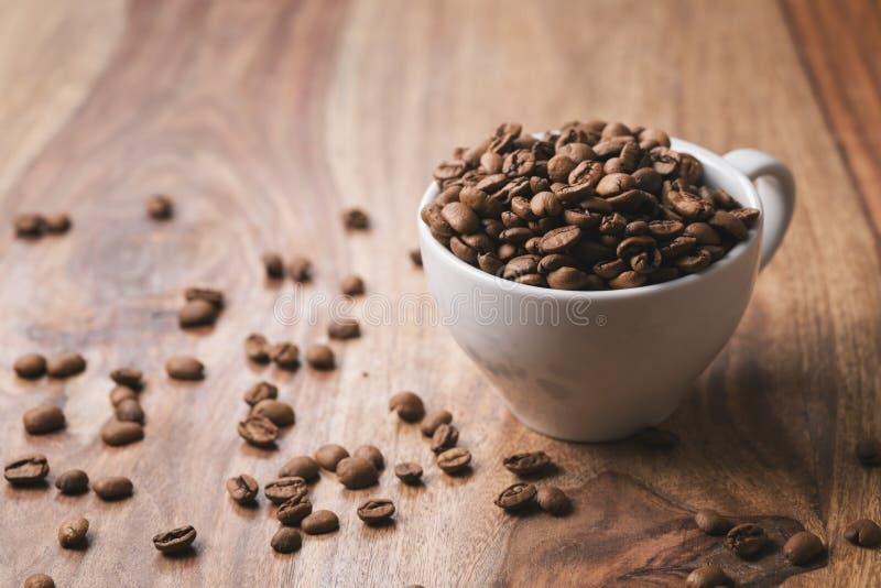 Kaffeebohnen, die in Kaffeetasse auf hölzerner Tabelle fallen lizenzfreie stockbilder