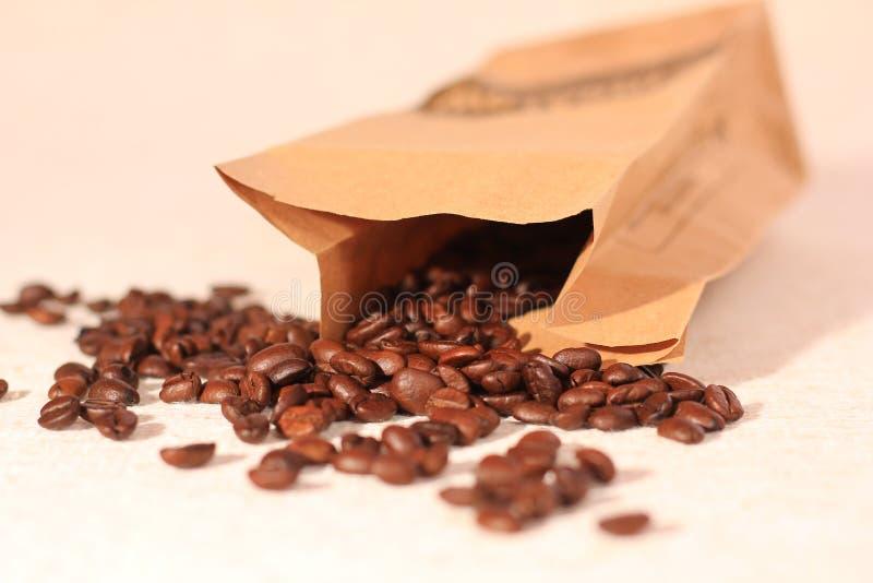Kaffeebohnen, die vom Papierbeutel überlaufen stockfotografie