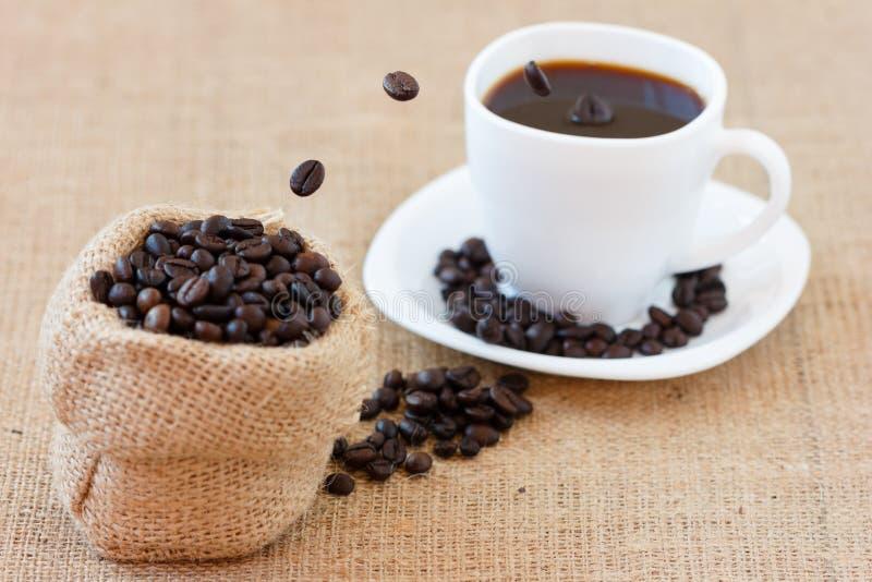 Kaffeebohnen, die in weiße Schale springen lizenzfreie stockfotografie