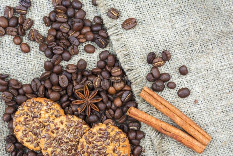 Kaffeebohnen, eine Scheibe der Zitrone, Zimtstangen und Plätzchen sind auf dem alten Leinengewebe lizenzfreie stockfotos