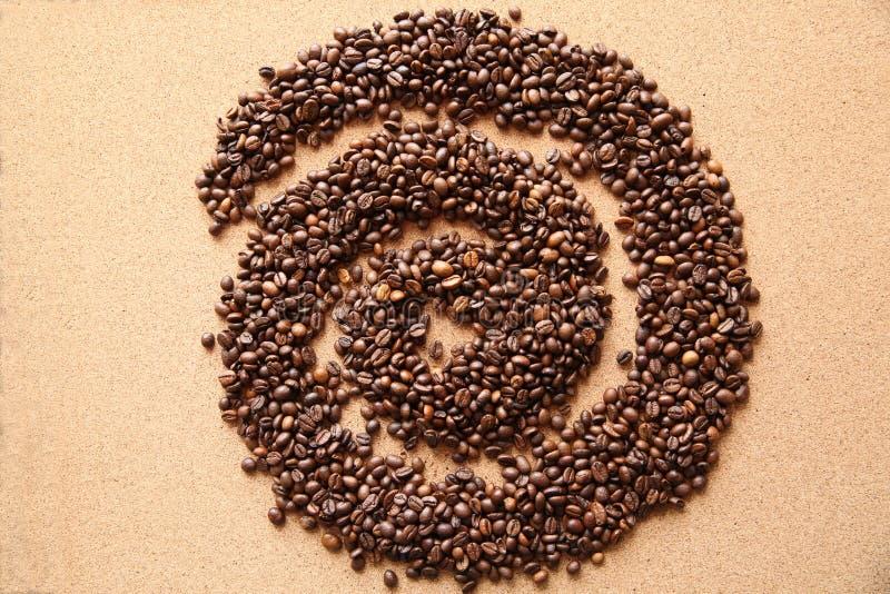 Kaffeebohnen in Form der Spirale auf hölzernem Hintergrund stockbilder