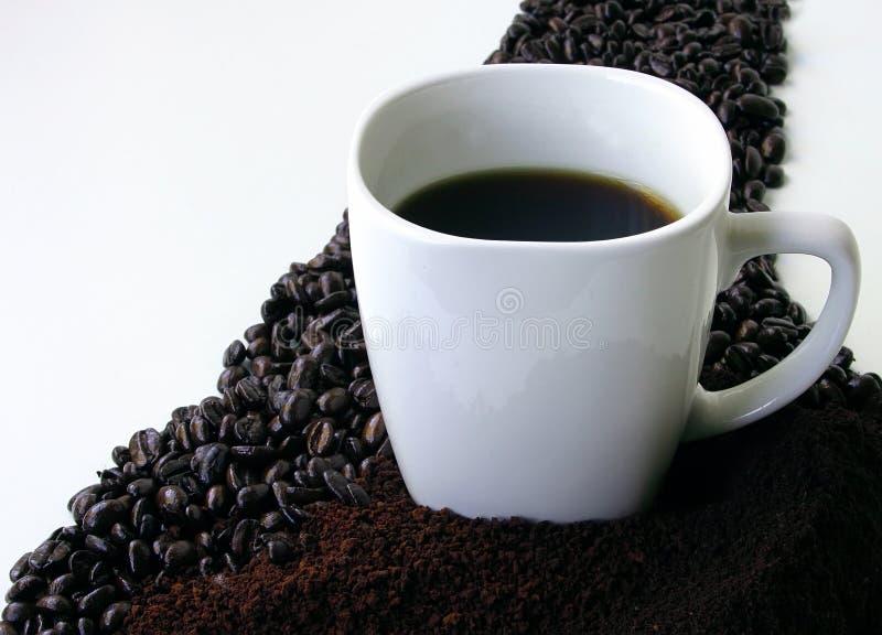 Kaffeebohnen, geerdeter Kaffee und eine Kaffeetasse lizenzfreies stockbild