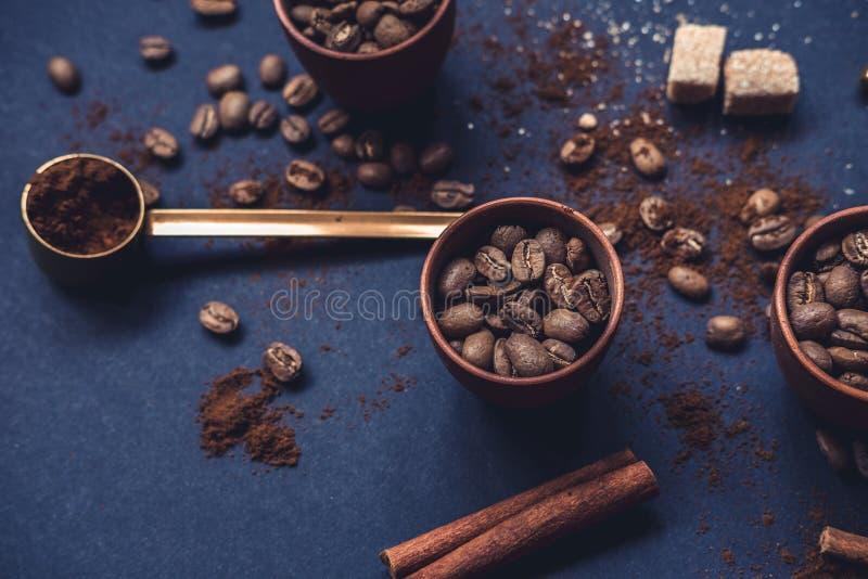 Kaffeebohnen im keramischen Schalen- und gemahlenemkaffee auf einem dunklen Hintergrund Beschneidungspfad eingeschlossen stockbild