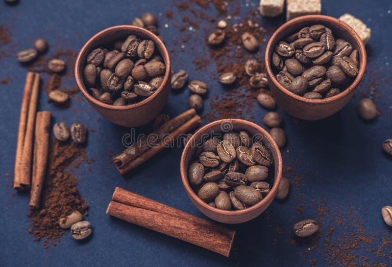 Kaffeebohnen im keramischen Schalen- und gemahlenemkaffee auf einem dunklen Hintergrund Beschneidungspfad eingeschlossen lizenzfreie stockfotografie