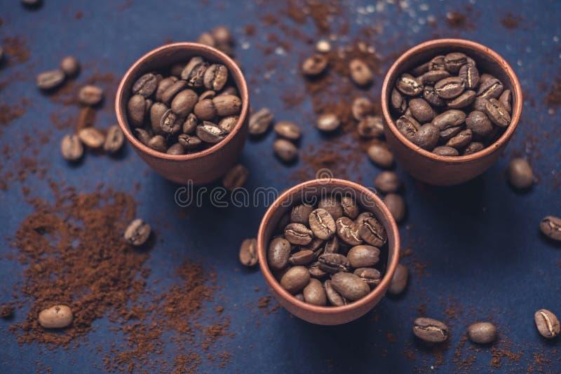 Kaffeebohnen im keramischen Schalen- und gemahlenemkaffee auf einem dunklen Hintergrund Beschneidungspfad eingeschlossen stockfotos