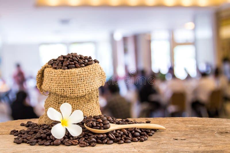 Kaffeebohnen im Leinwandsack auf Holztisch mit Unschärfehintergrund lizenzfreie stockfotos