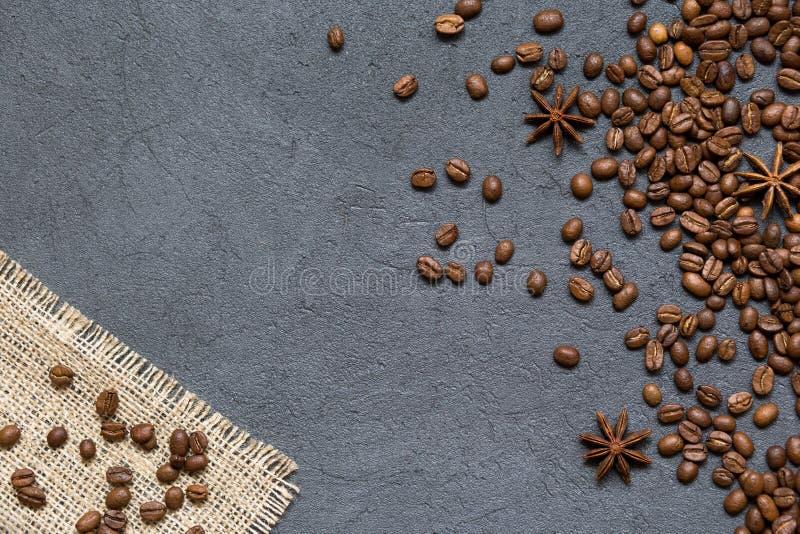 Kaffeebohnen und Bestandteile auf schwarzem Steinhintergrund, Draufsicht stockbilder