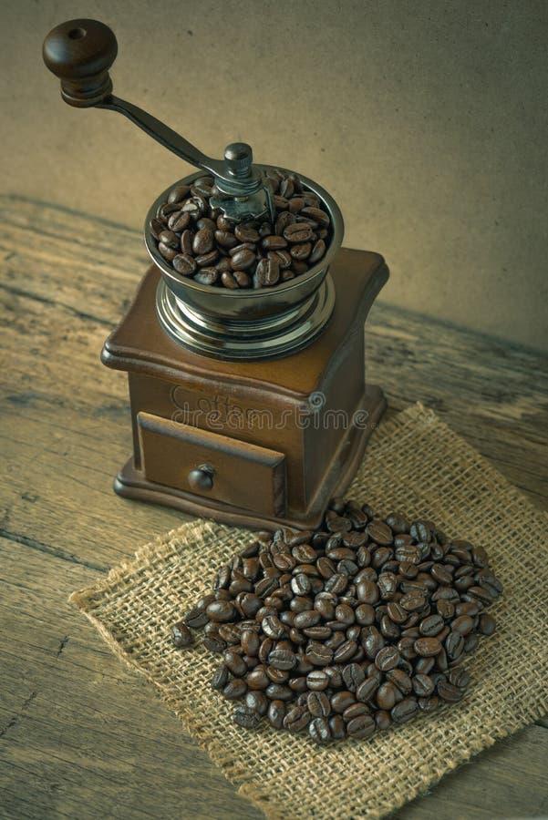 Kaffeebohnen und Kaffeemühle auf dem Holz stockfoto