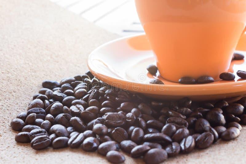 Kaffeebohnen und Tasse Kaffee auf braunem Gewebepapier stockfoto
