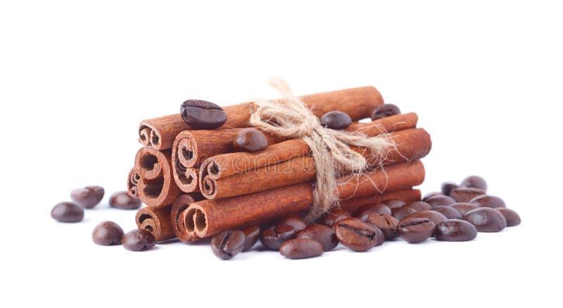 Kaffeebohnen und Zimtstangen lokalisiert auf weißem Hintergrund stockfotos