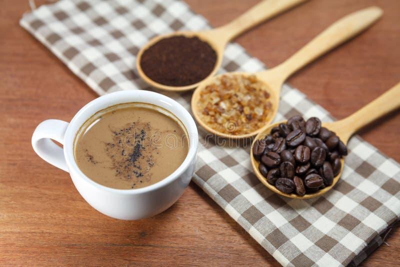 Kaffeebohnen und Zucker im hölzernen Löffel lizenzfreie stockbilder