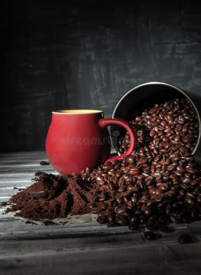 Kaffeebohnen wurden aus einer Blechdose auf einen Holztisch heraus verschüttet Nahe dem Burgunder-Schalen- und frisch gemahlenenk lizenzfreie stockfotos