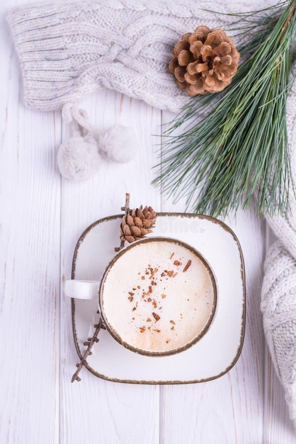 Kaffeecappuccino mit Ceylon-Zimt, einer Niederlassung einer Kiefers und gestrickten Zusätzen auf einem weißen hölzernen Hintergru lizenzfreie stockfotos